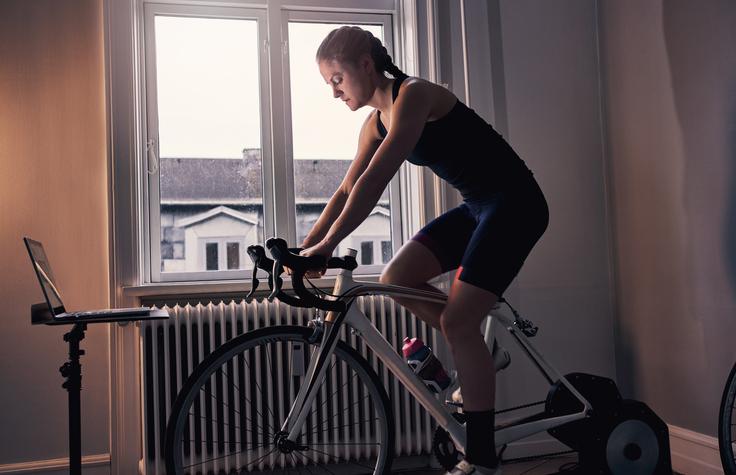 Chica pedaleando bicicleta estática en casa