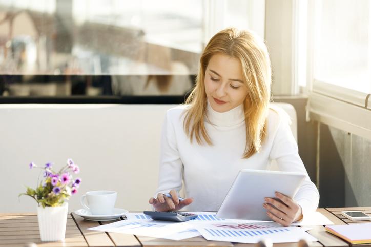 Mujer con jersey blanco revisando papeles
