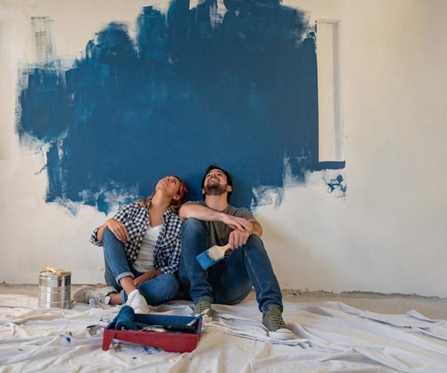 chica chico pintando pared azul