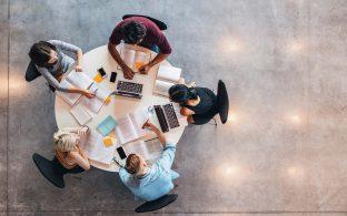 Cinco personas trabajando en una mesa redonda