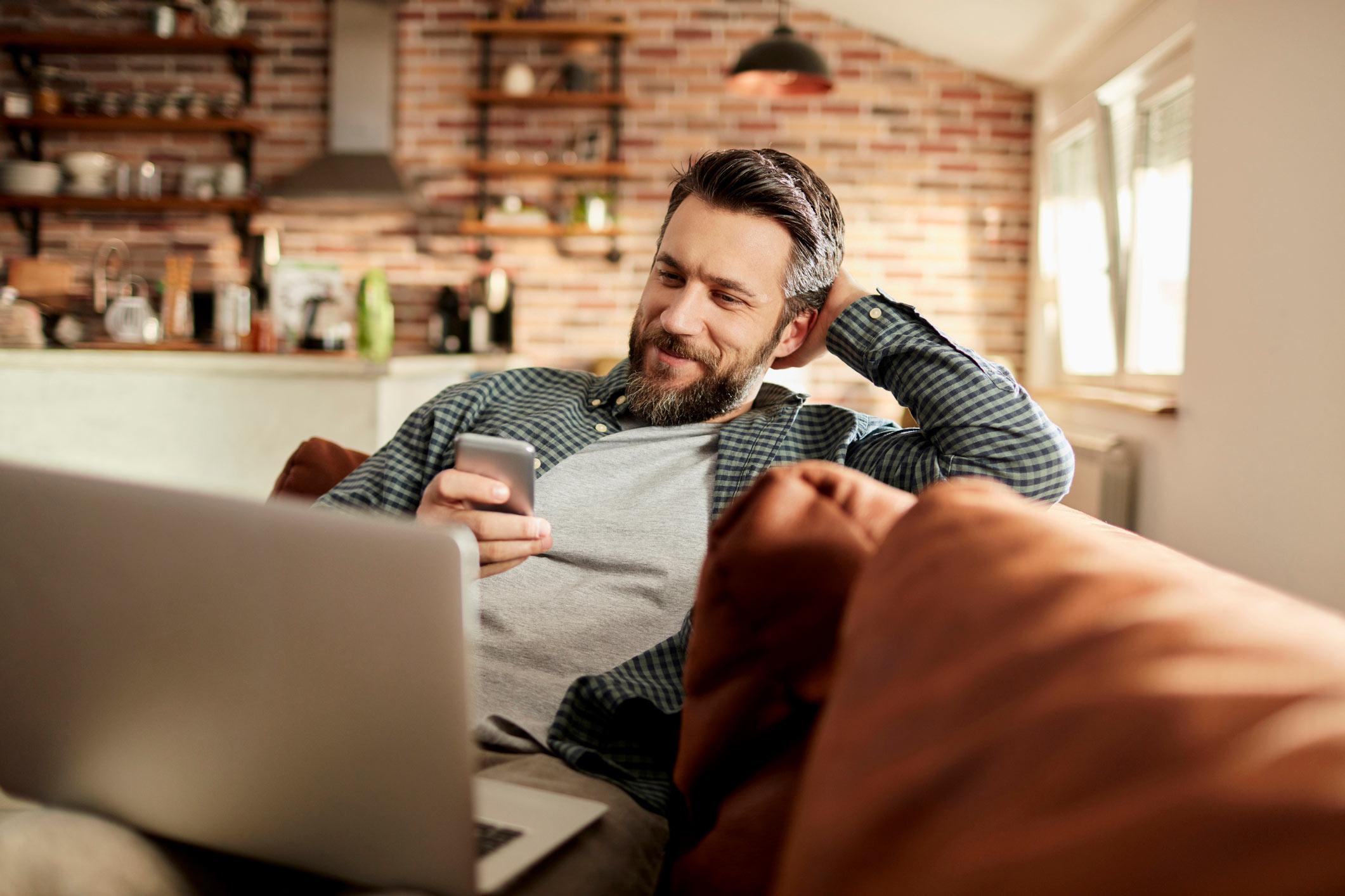 Hombre en el sofá con el móvil y portátil