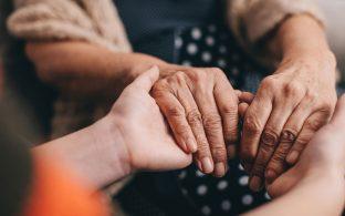 Manos de joven cogiendo manos de anciana